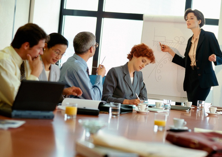 Group Of Business People In Conference Room, Businesswoman Pointing At Presentation Board