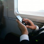 Businessman using PDA on train