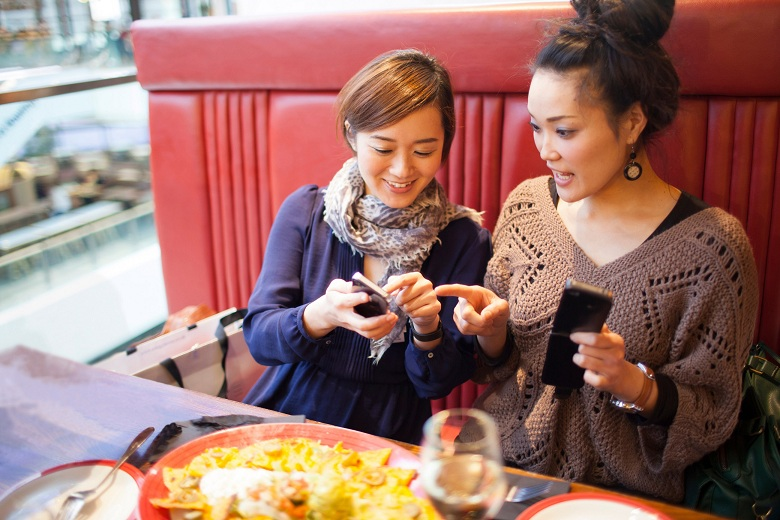 Young women using cell phones in restaurant