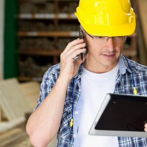 Hispanic carpenter using cell phone and digital tablet