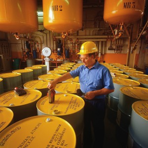 Worker Labeling Chemical Drums