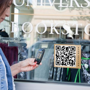 USA, Illinois, Peoria, Woman with smartphone reading barcode from window display