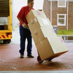 Young delivery man wheeling stack of boxes on sack barrow