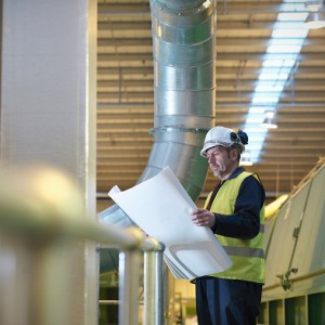 Worker With Plans In Plant