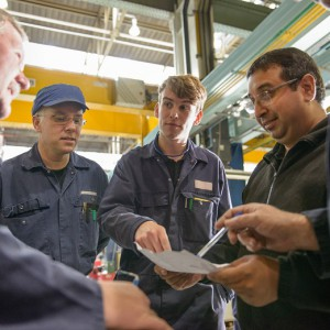 Apprentices talking in factory