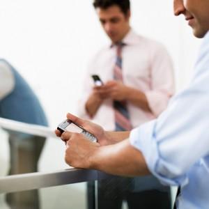 Businessman Using PDA in Hallway