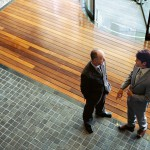 High Angle View of Two Businessmen Standing and Talking to Each Other in an Office