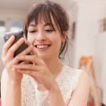 Young woman smiling and looking at a mobile phone at home