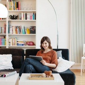 Stylish woman in modern livingroom working on a tablet