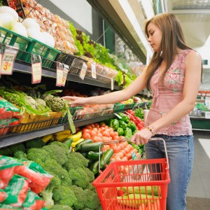 Woman selecting produce at supermarket, Perth, Australia