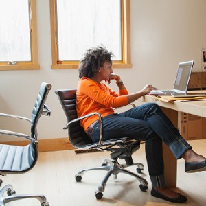 Woman sitting in room using laptop