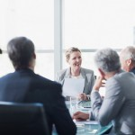 Smiling businesswoman leading meeting in conference room --- Image by © Ocean/Corbis