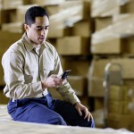 Man Using Cell Phone in Warehouse --- Image by © Tim Pannell/Corbis