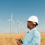 Oregon, USA --- USA, Oregon, Wasco, Engineer standing in wheat field in front of wind turbines, using digital tablet --- Image by © Erik Isakson/Tetra Images/Corbis