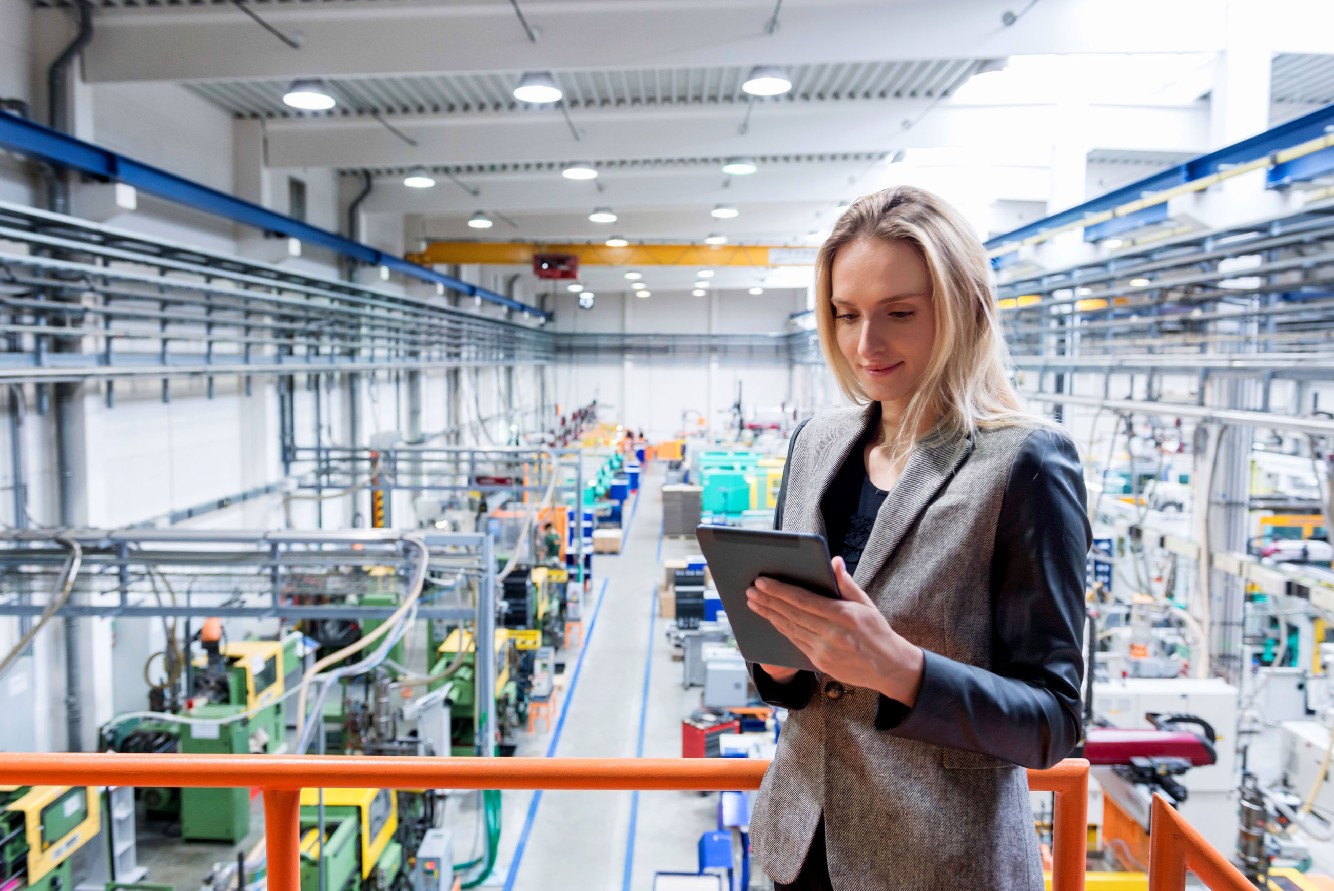 Horizontal color image of blond business female worker standing on balcony on top of large factory, holding digital tablet and examining the production online. Focus on attractive businesswoman, futuristic machines in background.